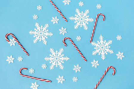 christmas, snow and winter holidays concept - white snowflakes and candy cane decorations on blue background Reklamní fotografie