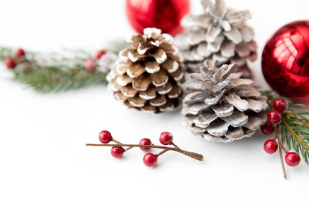 winter holidays, new year and decorations concept - red christmas balls and fir branches with pine cones on white background