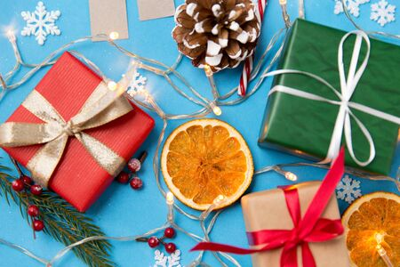 winter holidays, new year and christmas concept - gift boxes, garland lights and decorations on blue background