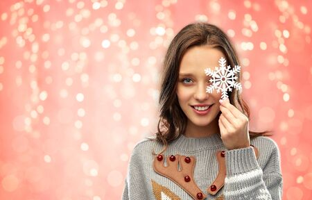 christmas, people and holidays concept - happy young woman with snowflake decoration wearing ugly sweater over festive lights on pink coral background