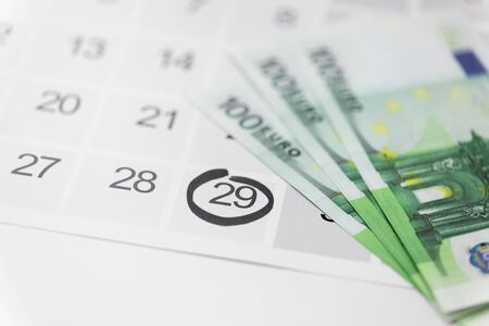 shopping, sale and marketing concept - close up of black friday date on calendar and money Фото со стока