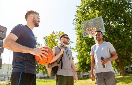 deporte, juegos de ocio y concepto de amistad masculina: grupo de hombres o amigos que van a jugar baloncesto al aire libre
