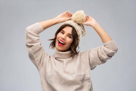 Concepto de Navidad, temporada y personas - mujer joven sonriente feliz con gorro de invierno de punto y suéter sobre fondo gris
