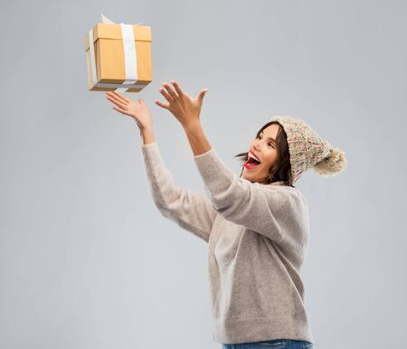 christmas, holidays and people concept - happy smiling young woman in knitted winter hat and sweater catching gift box over grey background