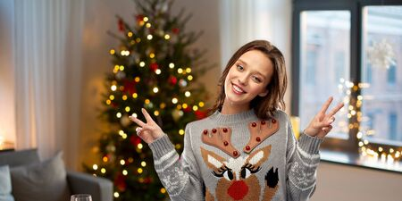christmas, party and holidays concept - happy young woman wearing ugly sweater with reindeer pattern showing peace over home background
