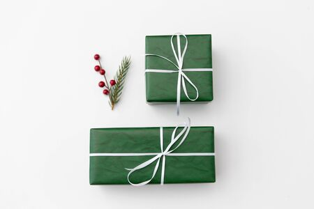 green gift boxes and fir tree branch with berries