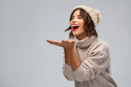 young woman in knitted winter hat sending air kiss Foto de archivo