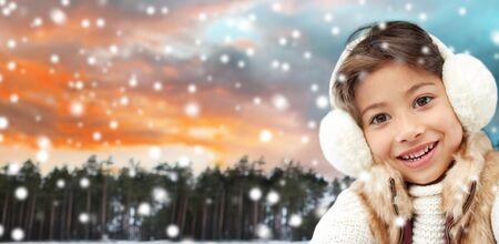happy little girl in earmuffs over winter forest Reklamní fotografie