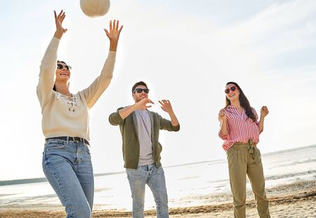 Amigos jugando voleibol en la playa en verano