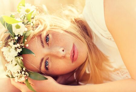 nature, summer holidays, vacation and people concept - face of happy woman in wreath of flowers lying on cereal field