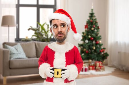 sad man in santa claus costume over christmas tree