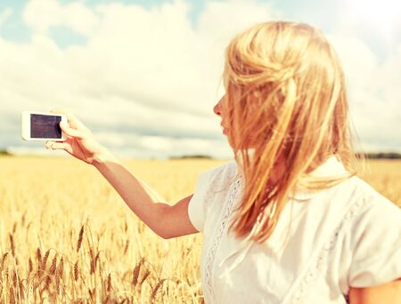 close up of girl with smartphone on cereal field Фото со стока