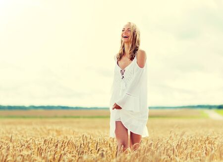 smiling young woman in white dress on cereal field Фото со стока
