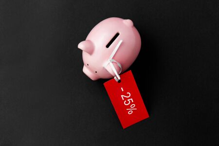 piggy bank with red sale tag on black 写真素材