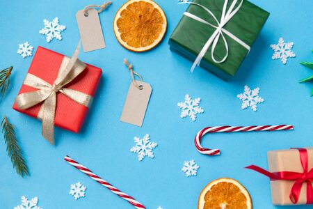 winter holidays, new year and christmas concept - gift boxes, fir tree branches, tags and decorations on blue background 版權商用圖片 - 131855142