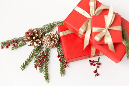 winter holidays, christmas and celebration concept - red gift boxes and fir tree branches with pine cones on white background