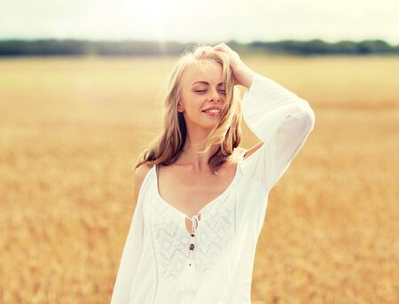 smiling young woman in white dress on cereal field 版權商用圖片