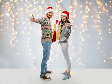 happy couple in christmas sweaters with gifts Stockfoto - 132026850