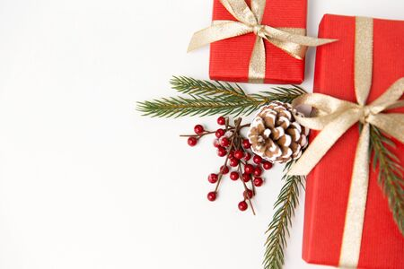 winter holidays, christmas and celebration concept - red gift boxes and fir tree branches with pine cones on white background Standard-Bild - 131971500