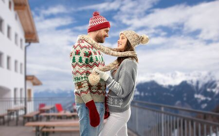 couple in ugly christmas sweaters over ski resort Stock Photo