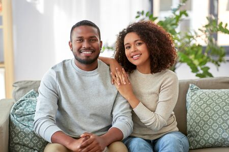 happy african american couple on sofa at home Stockfoto - 132026960