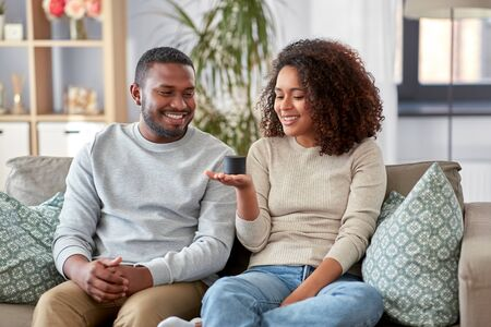african american couple with smart speaker at home Stockfoto