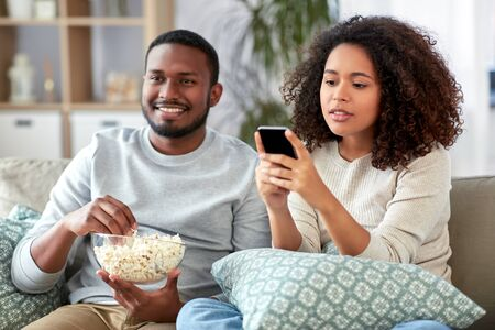 african couple with popcorn watching tv at home Stockfoto
