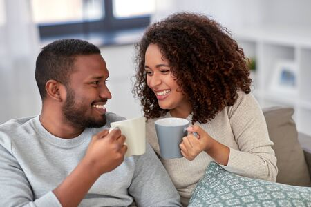 african american couple drinking coffee at home Stockfoto - 132026975
