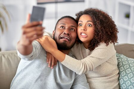 couple with smartphone taking selfie at home