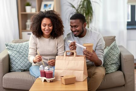 happy couple with takeaway food and drinks at home Stockfoto - 132027020