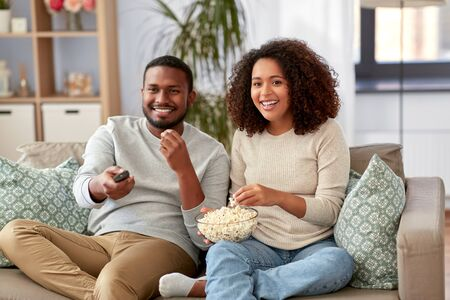 african couple with popcorn watching tv at home Stockfoto - 132027035
