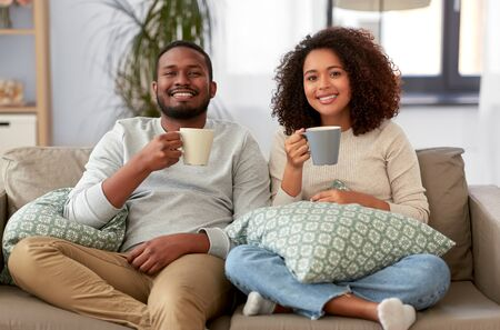 african american couple drinking coffee at home