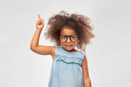 happy little african american girl in glasses