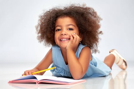 happy little african american girl with sketchbook Zdjęcie Seryjne