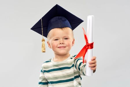 smiling little boy in mortar board with diploma