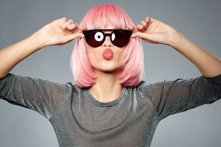 style, fashion and people concept - happy young woman in pink wig and black sunglasses sending air kiss to camera over grey background 版權商用圖片