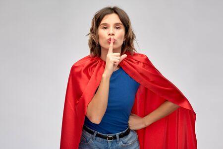 happy woman in red superhero cape