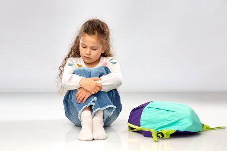 sad little girl with school bag sitting on floor Stockfoto - 132027234