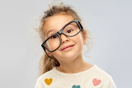 smiling little girl in crookedly placed glasses Stock Photo