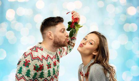 happy couple kissing under mistletoe on christmas