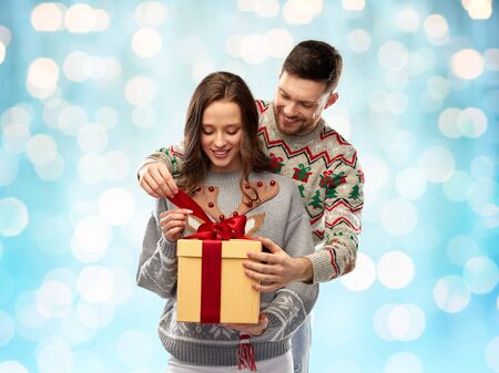 happy couple in christmas sweaters with gift box Stockfoto - 132300716