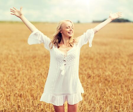 smiling young woman in white dress on cereal field 写真素材