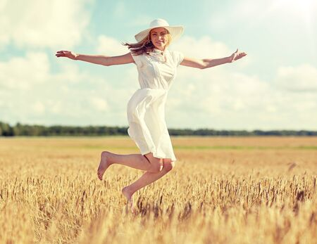 happy young woman jumping on cereal field