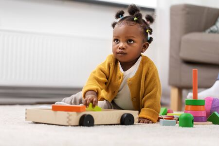 african baby girl playing with toy blocks at home