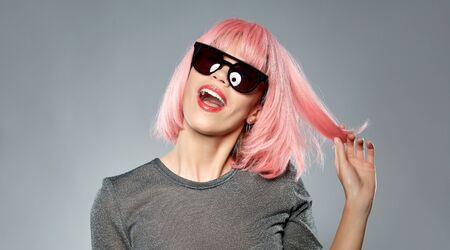 happy woman in pink wig and black sunglasses
