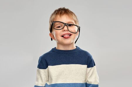 portrait of little boy in glasses showing tongue
