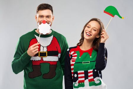 Couple with christmas party props in ugly sweaters 版權商用圖片