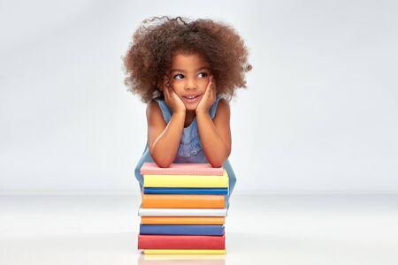 Lächelndes kleines afroamerikanisches Mädchen mit Büchern Standard-Bild