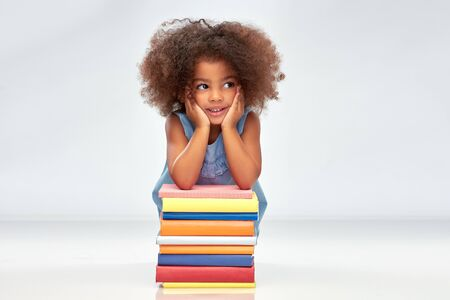 Smiling little african american girl with books Imagens