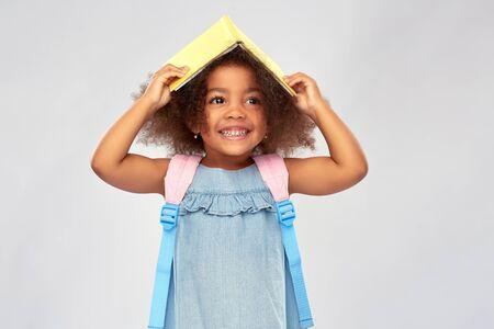 Glückliches kleines afrikanisches Mädchen mit Buch und Rucksack